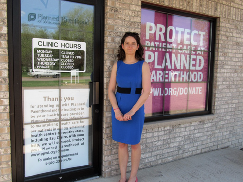 Nicole Safar, Planned Parenthood Public Policy Representative, standing next to the closing sign.  State budget cuts forced the closure of this Chippewa Falls health clinic on May 17, 2013.